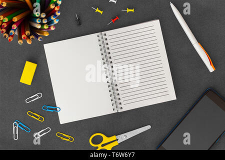 Open white line spiral paper notebook with mobile phone, pen, colored pencils, eraser, paper clips, push pins and scissors on empty dark background - Stock Photo