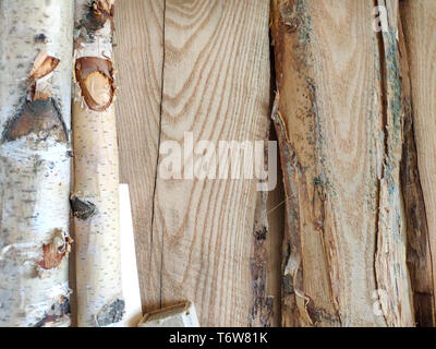 Wooden pillars and thick boards in the furniture workshop are ready to work joiner, soft focus - Stock Photo