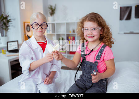 Curly girl eating ice cream with blonde friend wearing glasses - Stock Photo