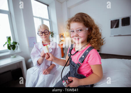 Funny girls wearing glasses eating glasses after playing together - Stock Photo