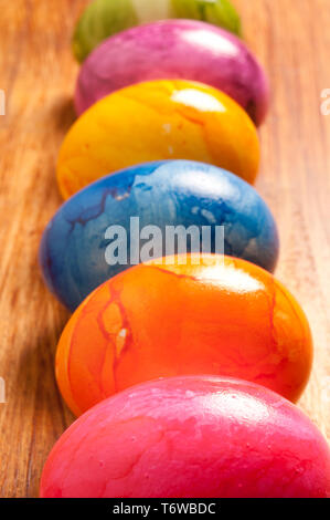 six colourful eggs in a row - Stock Photo