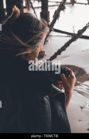 Asian woman wearing sunglasses on the beach with a camera - Stock Photo