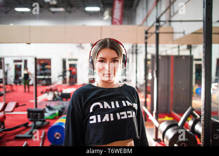 Attractive woman listening to music during a workout at the gym. - Stock Photo
