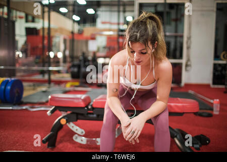 Fit blonde resting after an intense training session at the gym - Stock Photo