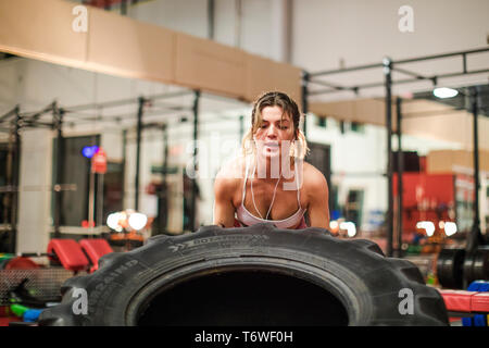 Young attractive woman lifting up a tractor tire - Stock Photo