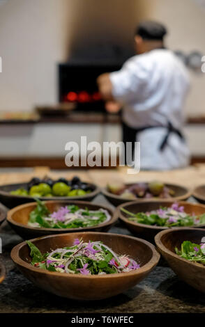 In soft focus in the background, chef puts pizza in pizza oven. In the foreground in focus, bowls of fresh salad. - Stock Photo
