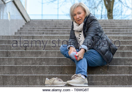 Helpless senior woman massaging her Foot - Stock Photo