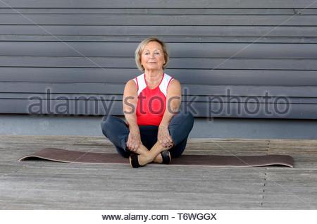 Senior woman doing exercises on a gym mat - Stock Photo