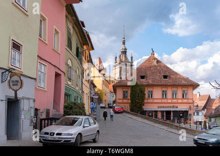 SIGHISOARA, ROMANIA - April 9, 2019: Colorful rooftops and houses in the centre of Sighisoara. Street scene on a sunny day with senior people walking
