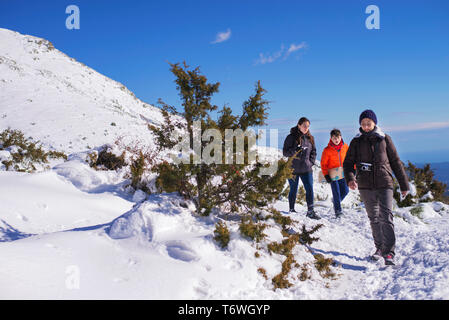 Three people walking on snow covered mountain in a sunny day - Stock Photo