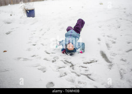 A happy child plays in the snow - Stock Photo