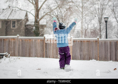 A joyful child raises arms to sky and plays in the snow - Stock Photo