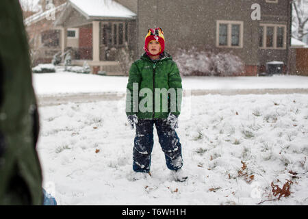 Front view of boy standing in a snowy yard in front of parent - Stock Photo