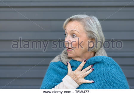 Startled elderly woman clasping her chest - Stock Photo