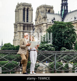 Couple of middle aged tourists looking at city map in front of Notre-Dame de Paris cathedral before the fire of April 15, 2019, Paris, France, Europe, - Stock Photo