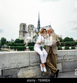 Couple of tourists in front of Notre-Dame cathedral, Paris, France, Europe - Stock Photo