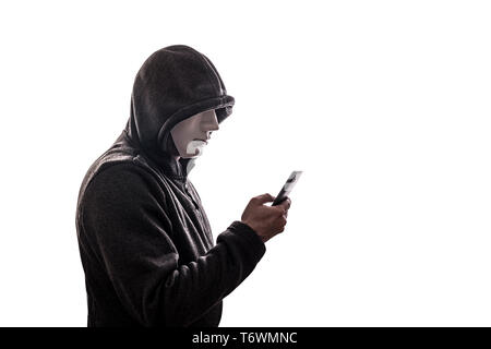 Hooded hacker with mask holding smartphone isolated on white background - Stock Photo