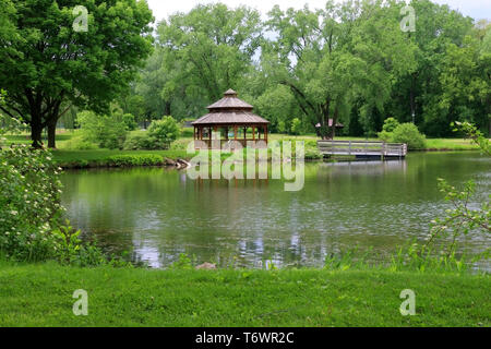 Beautiful late spring landscape with trees around the pond and wooden gazebo in a city park. Lakeview park, Middleton, Madison area, WI, USA. - Stock Photo