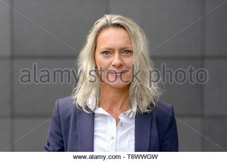 Mature blond woman looking intently at the camera - Stock Photo