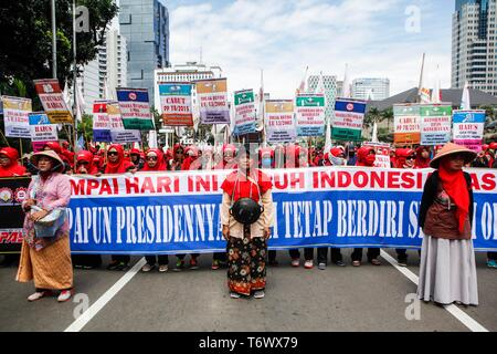 Labourers seen holding placards and a banner during the rally to mark International Workers' Day in Jakarta. Protesters across Indonesia have organized rallies to demand better working conditions. - Stock Photo