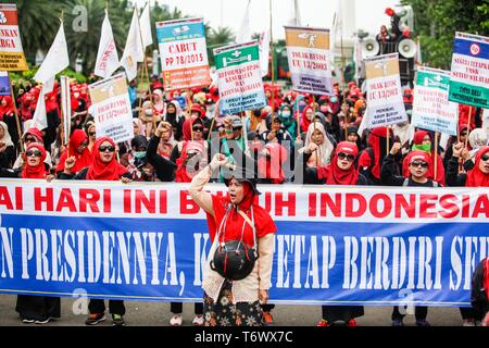 Labourers seen holding placards and a banner while chanting slogans during the rally to mark International Workers' Day in Jakarta. Protesters across Indonesia have organized rallies to demand better working conditions. - Stock Photo