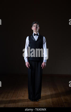 young dancer in the ballroom on a black background, classic dance - Stock Photo