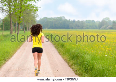 Fit muscular young woman jogging in farmland - Stock Photo