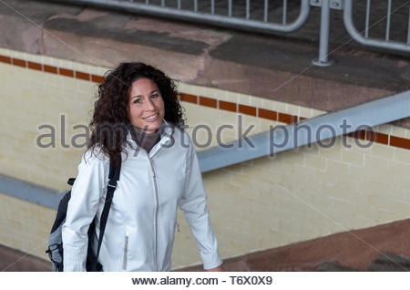 Attractive young woman climbing a flight of stairs - Stock Photo