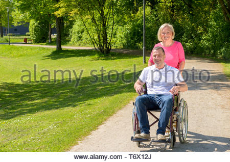 Man seated in wheel chair while wife pushes - Stock Photo