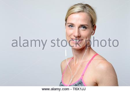 smiling young woman wearing earphones - Stock Photo
