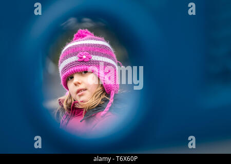 Young girl in a pink hat peeking through the hole - Stock Photo