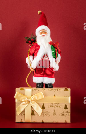 Santa Claus figure standing on a golden gift box - Stock Photo