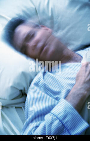 Mature man with insomnia tossing and turning at night, USA - Stock Photo