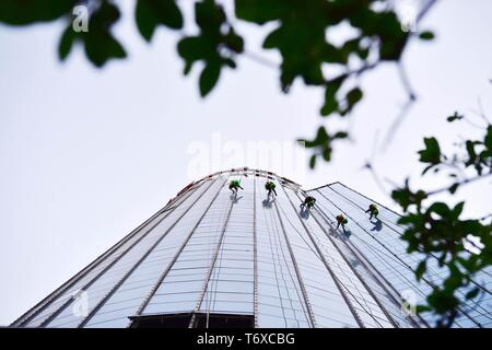 Zhengzhou, China's Henan Province. 2nd May, 2019. Workers clean the glass curtain wall of a skyscraper in Zhengzhou, capital of central China's Henan Province, May 2, 2019. Credit: Feng Dapeng/Xinhua/Alamy Live News - Stock Photo