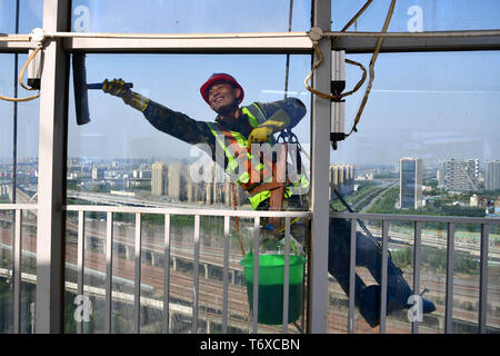 Zhengzhou, China's Henan Province. 2nd May, 2019. A worker cleans the glass curtain wall of a skyscraper in Zhengzhou, capital of central China's Henan Province, May 2, 2019. Credit: Feng Dapeng/Xinhua/Alamy Live News - Stock Photo