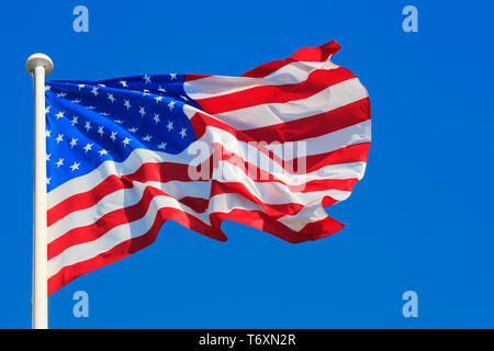 The flag of the United States of America (aka Stars and Strips aka Star-Spangled Banner aka the Old Glory) flying proudly over Normandy, France - Stock Photo