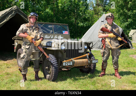 2 soldiers of the 101st Airborne Division with their Willys jeep during the D-Day commemorations in Normandy, France - Stock Photo