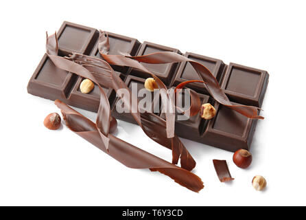 Delicious chocolate bar, shavings and hazelnuts on white background - Stock Photo
