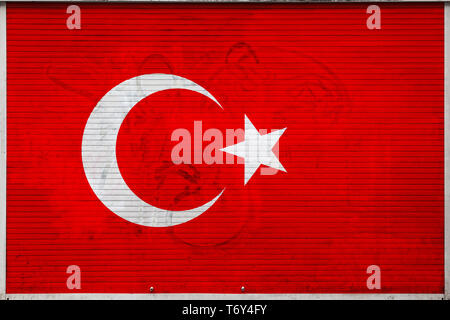 Close-up of old metal wall with national flag of Turkey. Concept of Turkey export-import, storage of goods and national delivery of goods. Flag in gru - Stock Photo