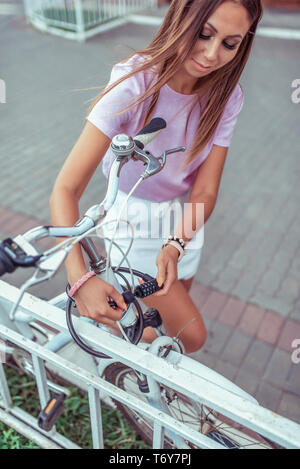 Brunette girl in the summer in city. Locks your bike. Parking and installation of cable and lock with code. Concept against theft and theft of a - Stock Photo