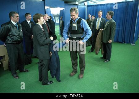 President George W Bush puts on a protective vest prior to throwing out the ceremonial first pitch in Game Three of the World Series between the Arizona Diamondbacks and the New York Yankees, Yankee Stadium in New York City, October 30, 2001. Courtesy National Archives. () - Stock Photo