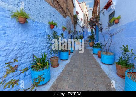 Blue street with color pots in Chefchaouen - Stock Photo