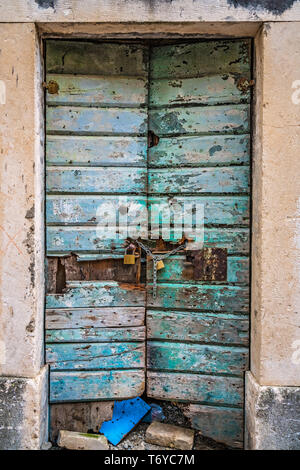 Locked old green damaged wooden doors - Stock Photo