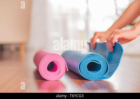 Attractive young woman folding yoga mat after workout at home. Woman rolling fitness mat after morning exercise - Stock Photo