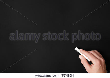 hand holding chalk against blank chalkboard background - Stock Photo