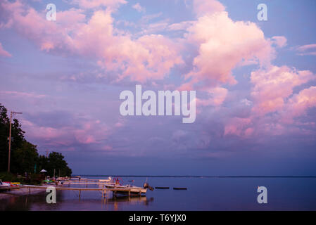 View of beautiful sky, a boat and docks on lake at sunset - Stock Photo