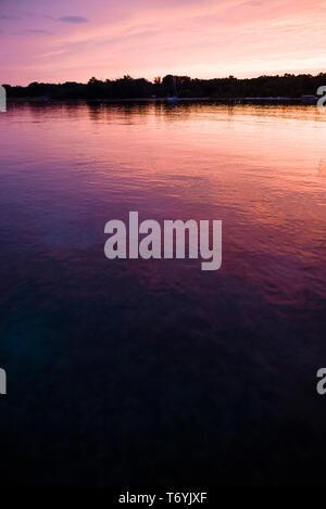 Pink hues of sunset reflecting on Lake Michigan - Stock Photo