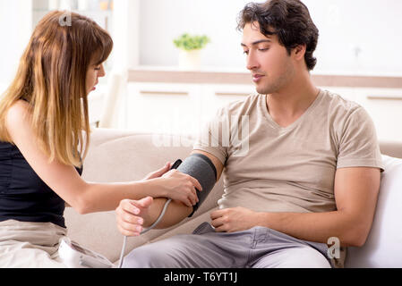 The wife checking husband's blood pressure - Stock Photo
