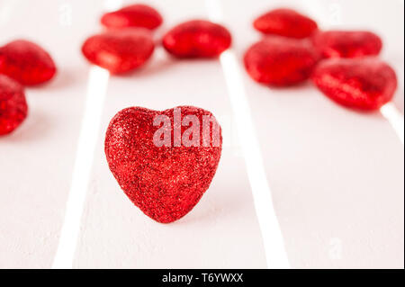 Many glitter red hearts on white wood background. - Stock Photo