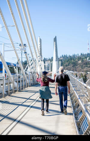 An elderly couple a man and woman taking care of their health take a walk on the Tilikum Crossing Bridge preferring an active lifestyle carrying a cha - Stock Photo